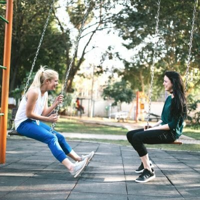 zwei junge frauen auf kinderspielplatz, sitzen auf Schaukeln und unterhalten sich , two young women sitting on swings on a playground talking to each other